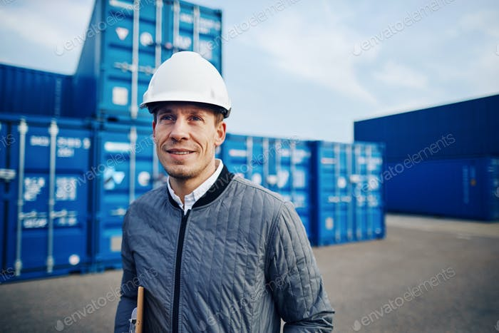 Smiling port manager standing on a large commercial shipping dock