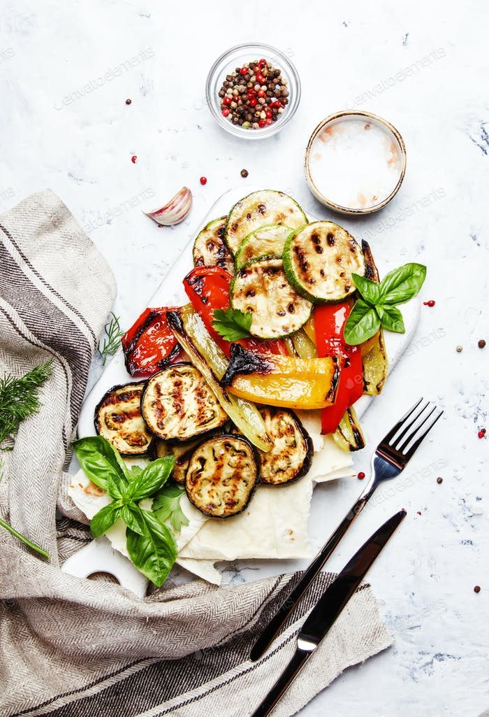 Grilled colorful vegetables, aubergines, zucchini, pepper with spice and green basil