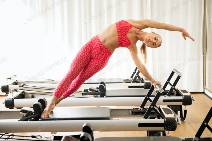 Woman exercising mermaid stretch on reformer bed