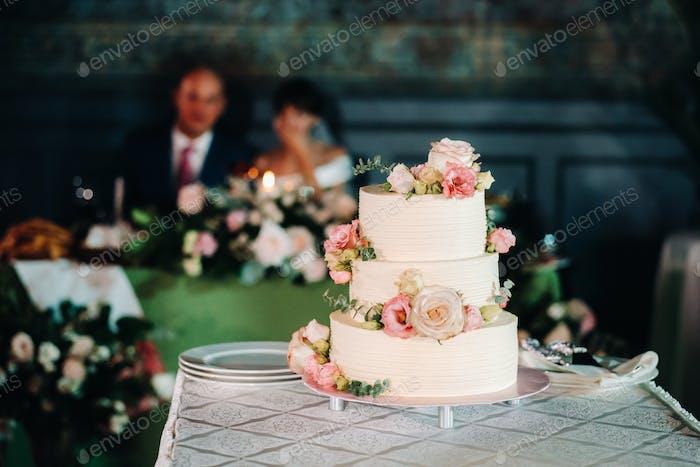 Elegant wedding cake at the wedding in three tiers