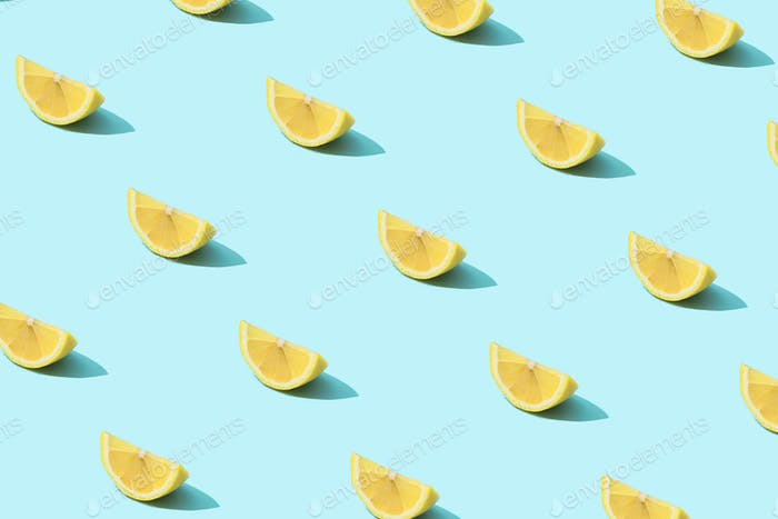 Trendy sunlight Summer pattern made with yellow lemon slice on bright light blue background.