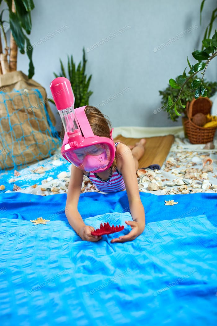 Little girl wearing snorkeling mask imitates swimming in fictional beach