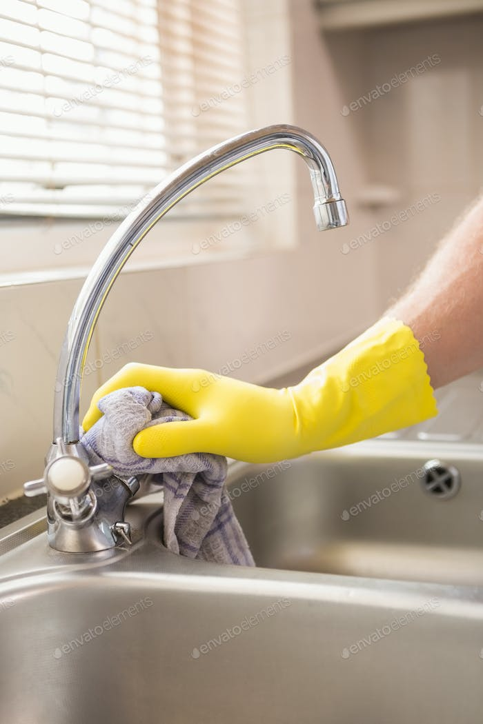 Hand cleaning a sink with cloth at home in the kitchen