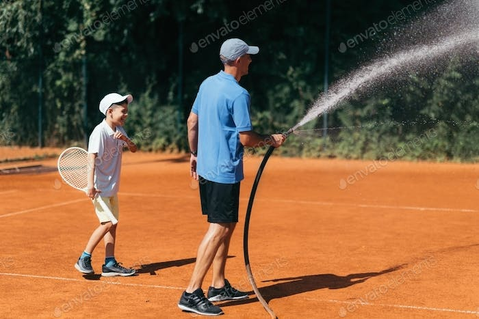 Tennis Coach Spraying a Clay Court with Water