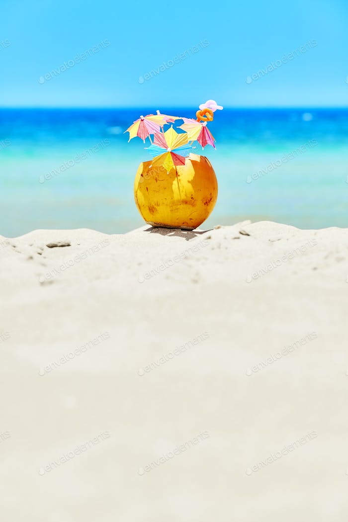 Coconut with colorful umbrellas and straws on a beach.