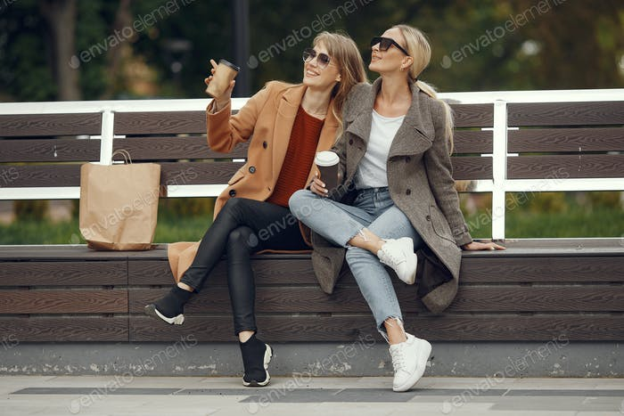 Mädchen sitzen in einem Frühjahr sity und halten Kaffee in der Hand