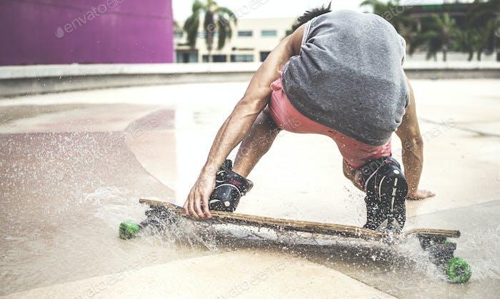 A skateboarder crouching down riding a skateboard through water.