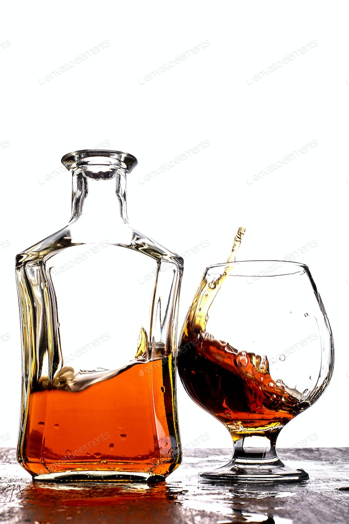 Glass of splash whiskey with bottle.