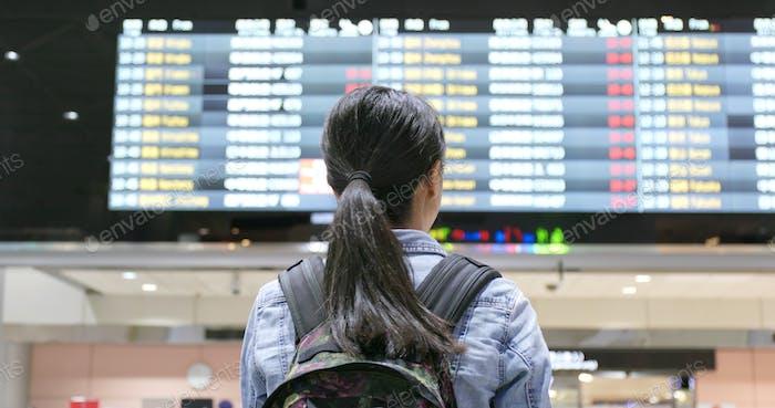 Viajera joven que busca el número de vuelo en el aeropuerto