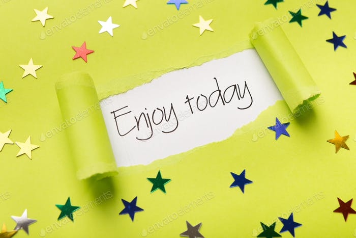 Enjoy today phrase showing up under torn yellow paper