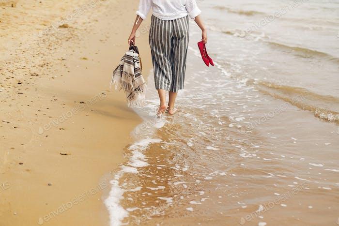 Woman walking barefoot on beach