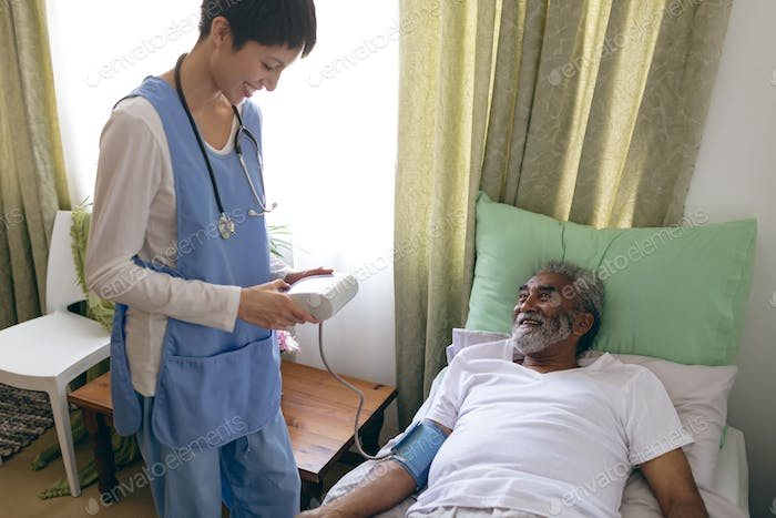 Asian female nurse checking blood pressure of African-american senior male patient