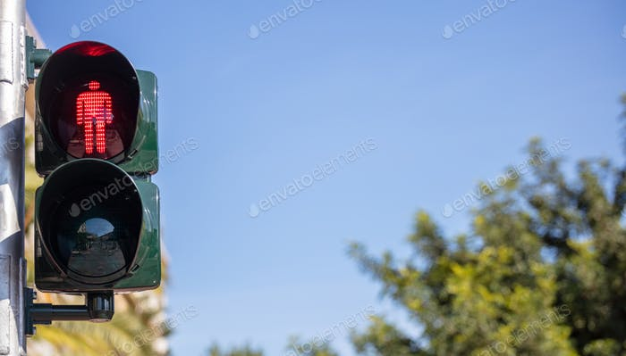 Red traffic lights for pedestrians, blue sky background