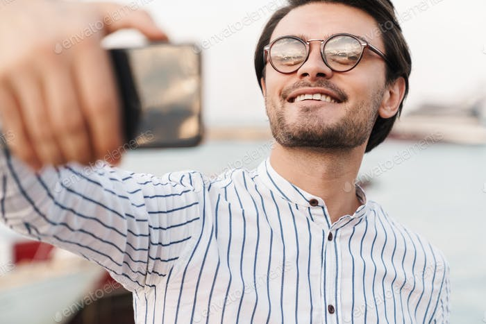 Photo of cheerful caucasian man taking selfie photo on smartphone and smiling while walking on pier