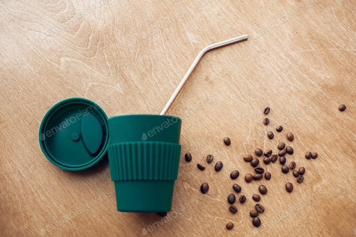 Stilvolle wiederverwendbare Eco-Kaffeetasse mit gerösteten Kaffeebohnen und grünem Monsterablatt