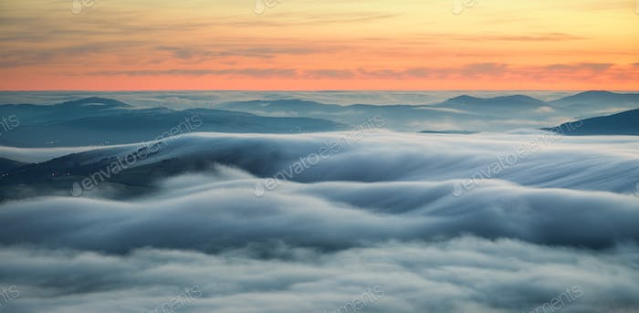 Wavy blankets of thick fog over valleys and hills