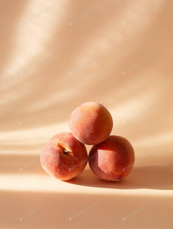 Frische Pfirsiche auf einem pastellfarbenen Hintergrund mit Schatten