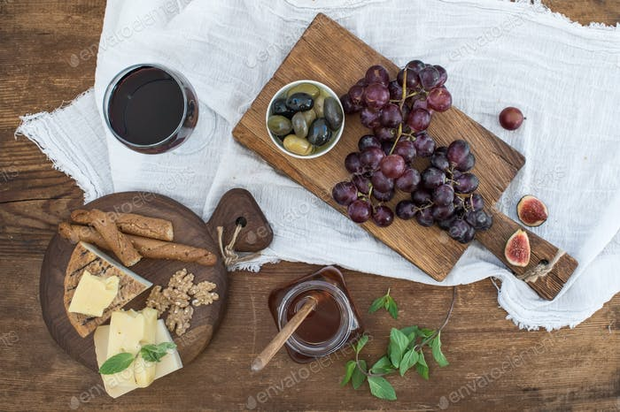 Glass of red wine, cheese board, grapes, walnuts, olives, honey and bread sticks