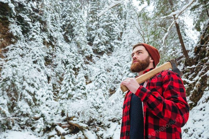 Schöner bärtiger junger Mann mit Axt im Winterwald