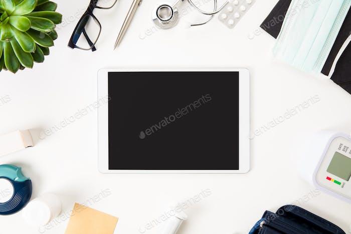 Tablet-Computer mit medizinischen Geräten auf dem Tisch