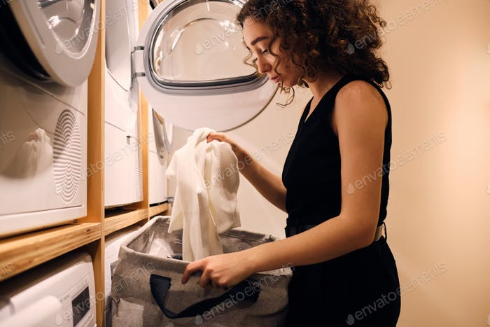 Side view of beautiful girl washing clothes in self-service laundry