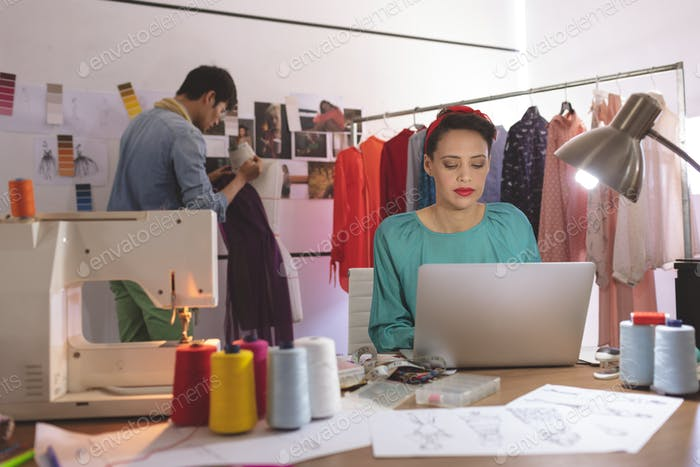 Female fashion designer working on laptop