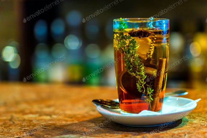 Tea with cinnamon, lemon and herb in glass
