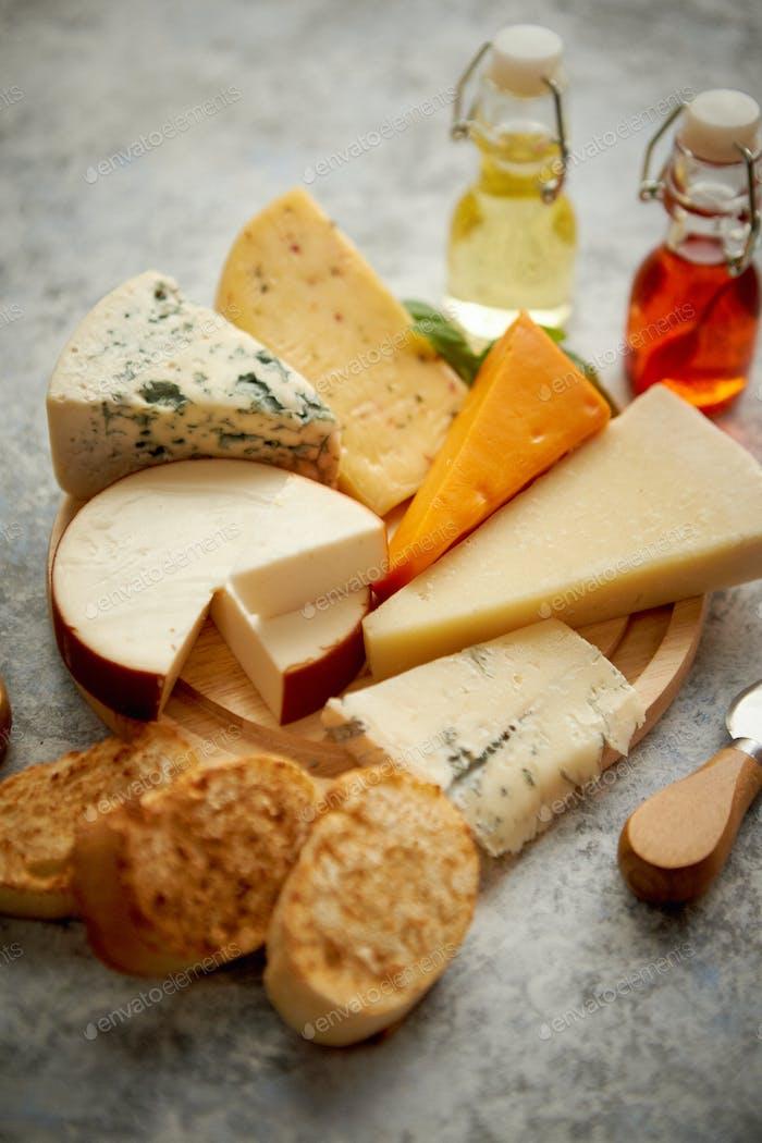 Verschiedene Arten von Käse serviert auf rustikalem Holzbrett