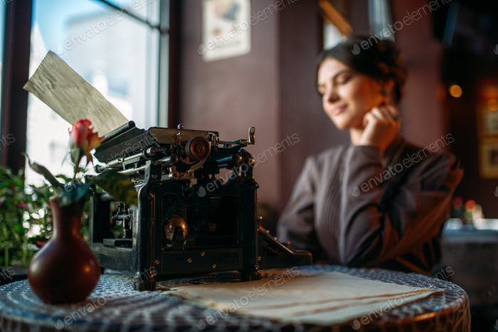 Smiling lady sits by table with ancient typewriter