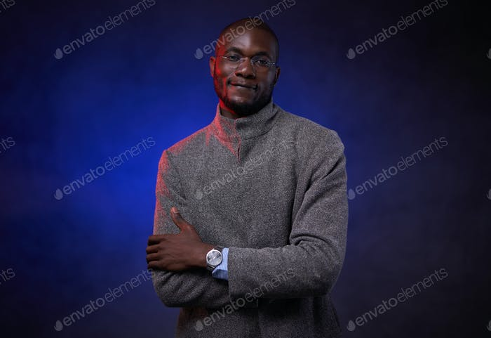 Stylish African American man in gray jacket and glasses on dark background with blue light