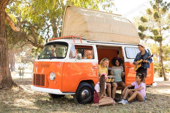 Happy friends enjoying music at camper van