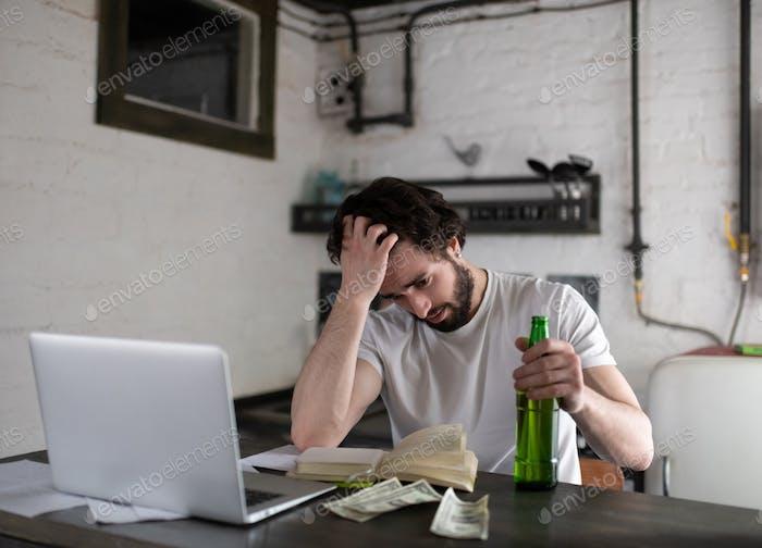 Бедный человек с пивом ищет работу