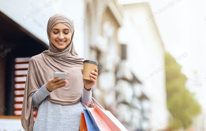 Cheerful muslim girl with shopping bags using phone