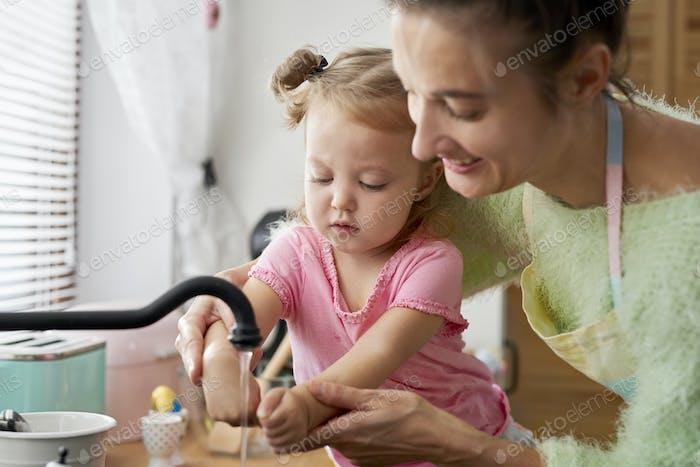 Baby Mädchen waschen ihre Hände in die Küche