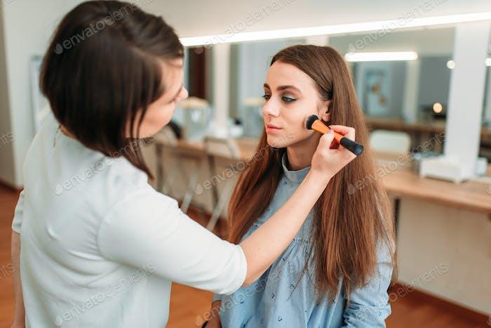 Female make up artist applying make-up with brush