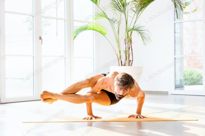 Man doing an Astavakrasana or eight-angle pose