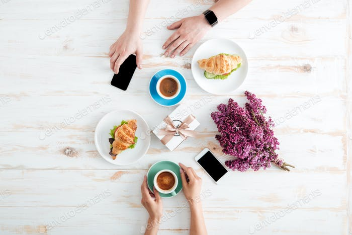 Hands of couple drinking coffee with croissants on wooden table