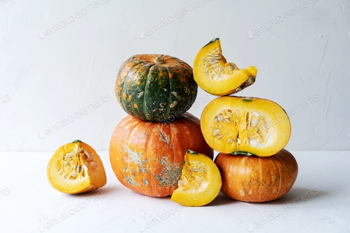 Close-up of beautiful ripe pumpkins and slices in autumn still life. Autumn content.