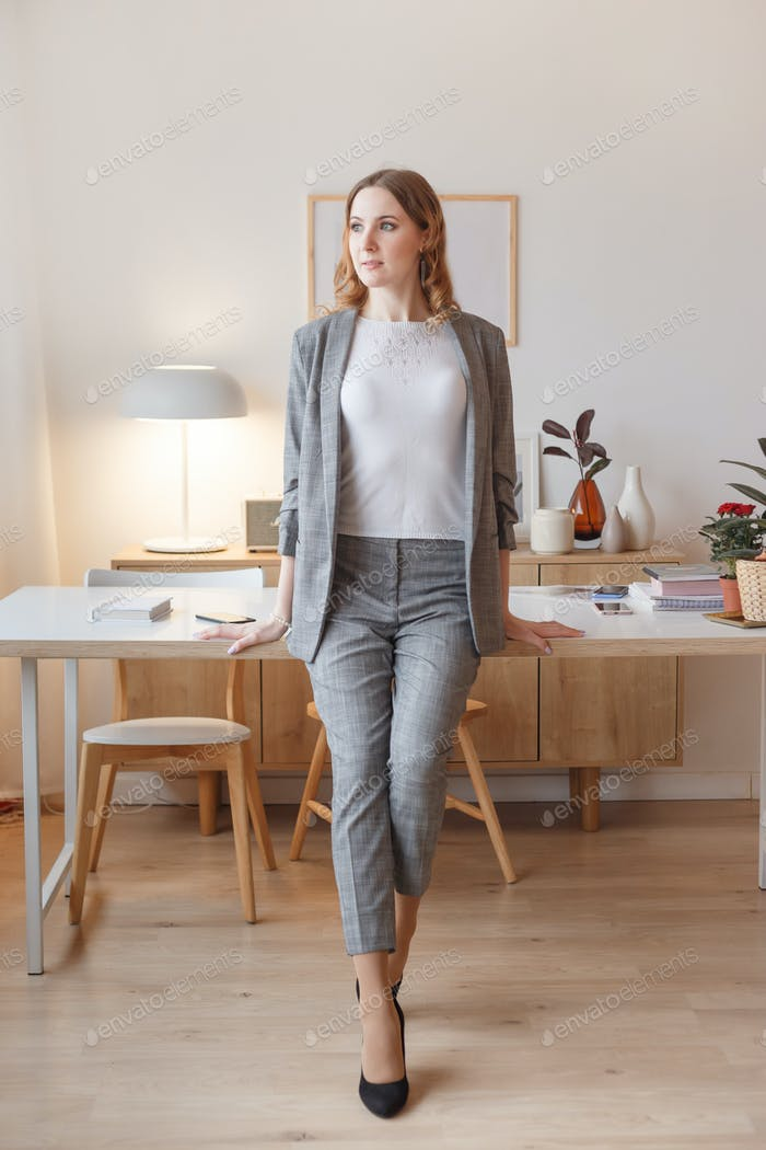 Young boss woman in a gray stylish suit stands in her own creative office