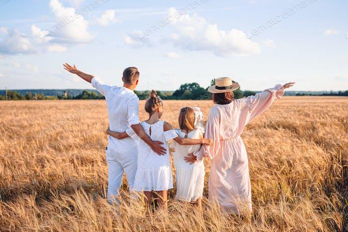 Familia feliz jugando en un campo de trigo