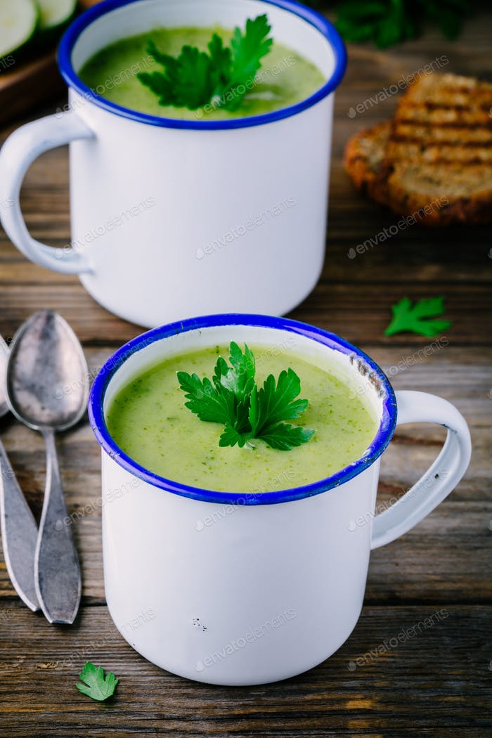 homemade green broccoli cream soup with parsley in mugs
