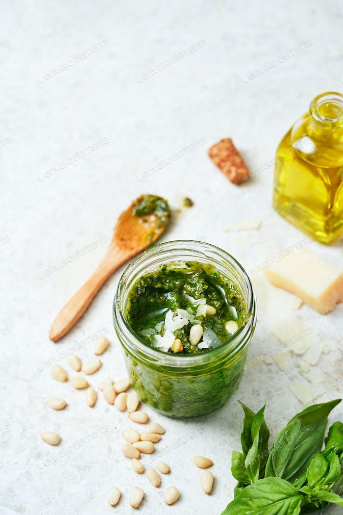 Pesto-Sauce mit Zutaten, frischem Basilikum, Pinienkernen, Knoblauch und Käse auf hellem Marbre Hintergrund.