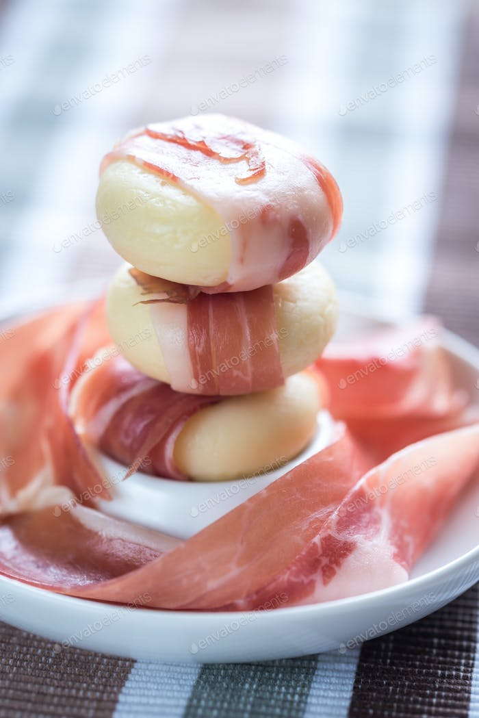 Mini cheese and prosciutto wraps on the plate