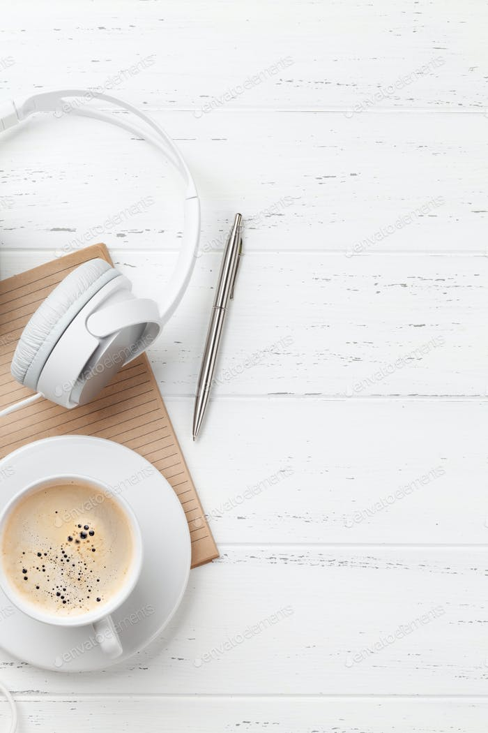 Office table with coffee cup, headphones and supplies