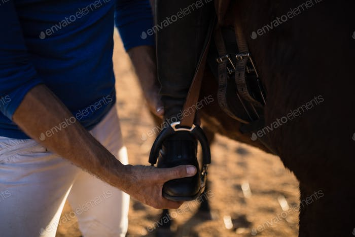 Midsection of male trainer adjusting woman leg on stirrup