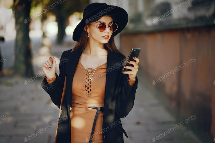 stilvolles Mädchen zu Fuß durch die Stadt, während mit ihrem Handy