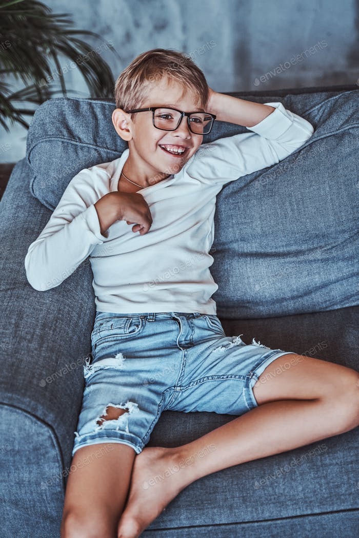 Smiley boy with glasses poses on sofa in living room