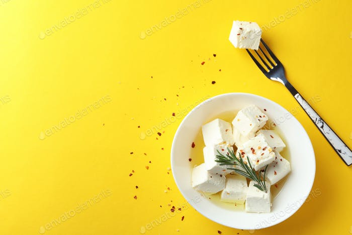 Bowl and fork with feta cheese on yellow background