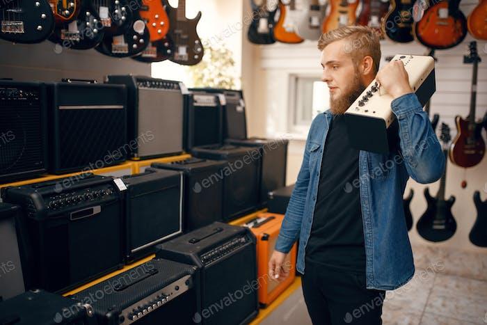 Young man choosing combo amplifier in music store