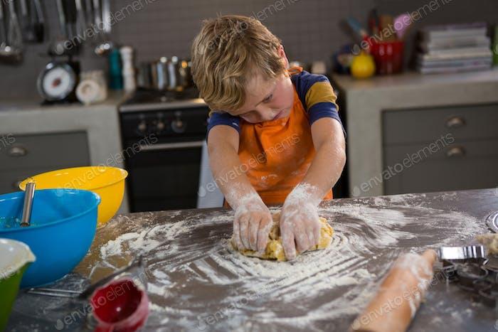 Boy kneading dough in kitchen